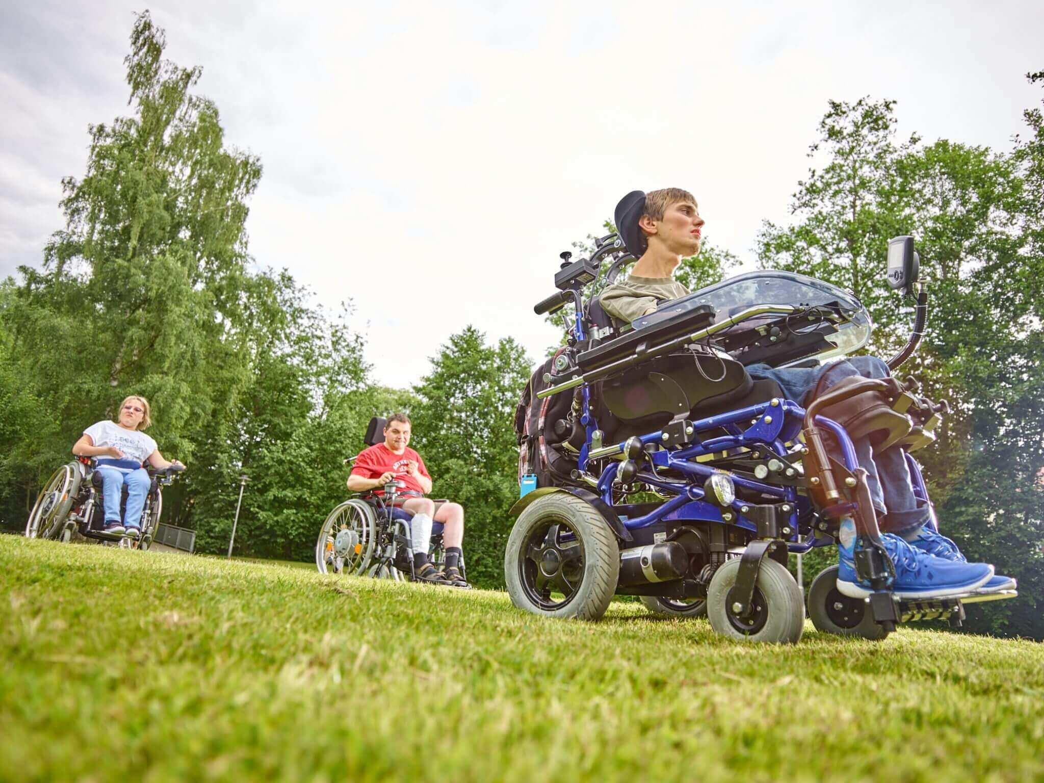 Drei junge Menschen im Rollstuhl im Kurpark Regen.
