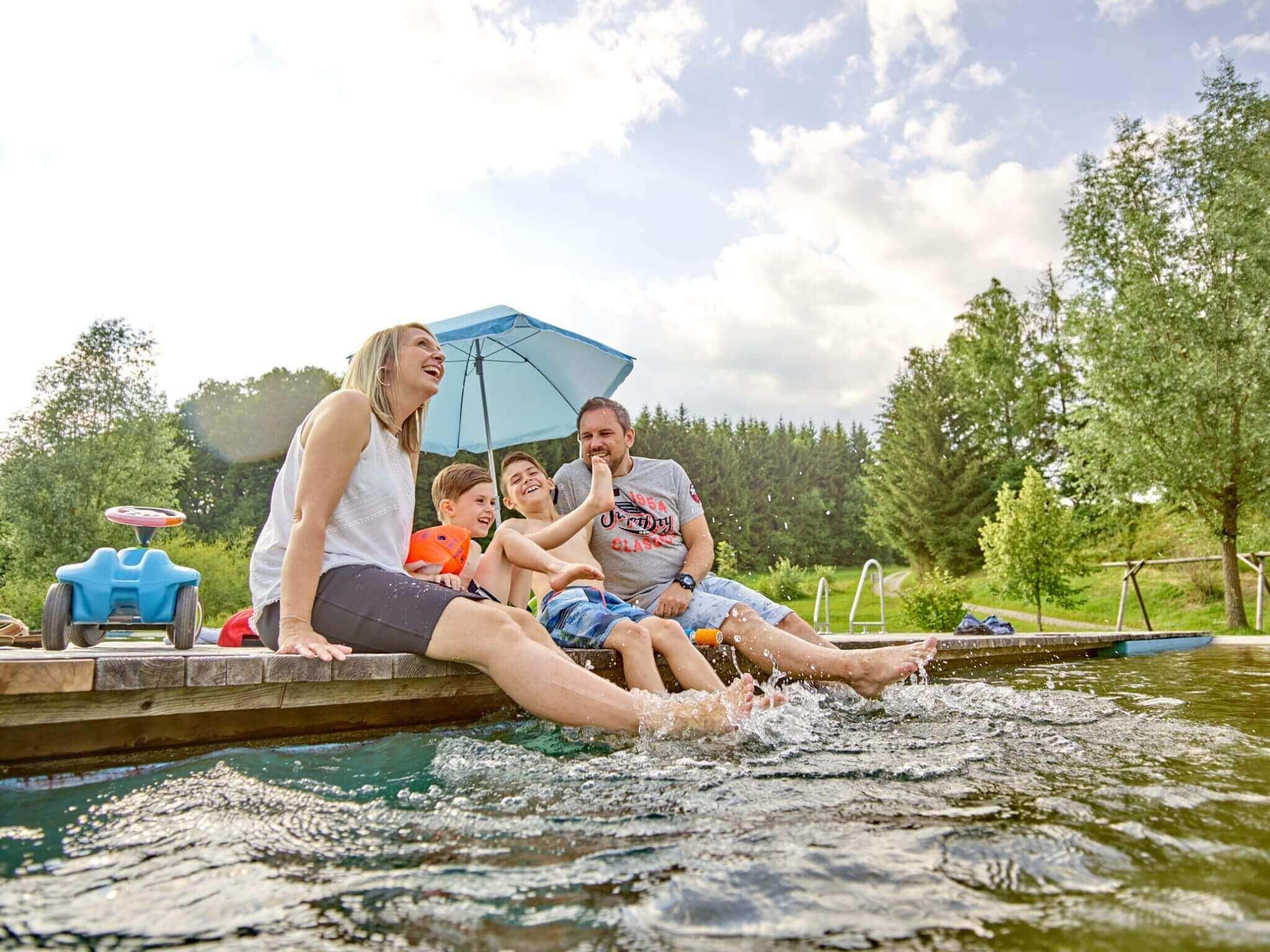 Eine junge Familie sitzt auf dem Steg am Naturbadeweiher Drachselsried und planscht mit den Füßen im Wasser. Im Hintergrund die Natur, ein Bobbycar zum spielen und ein Sonnenschirm.