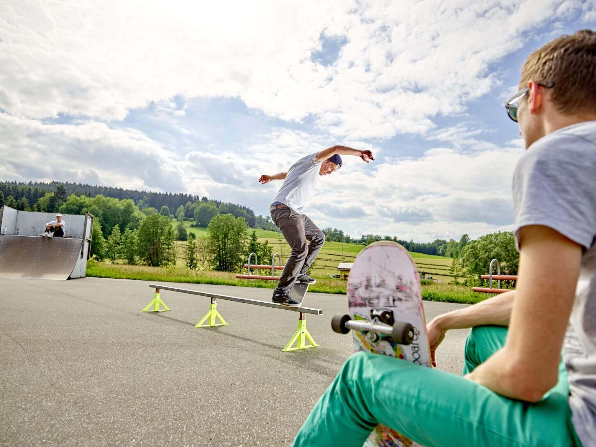 Ein jugendlicher Skater im Mittelpunkt, rechts ein zweiter Skater mit Skateboard in der Hand im Skatepark Zwiesel.