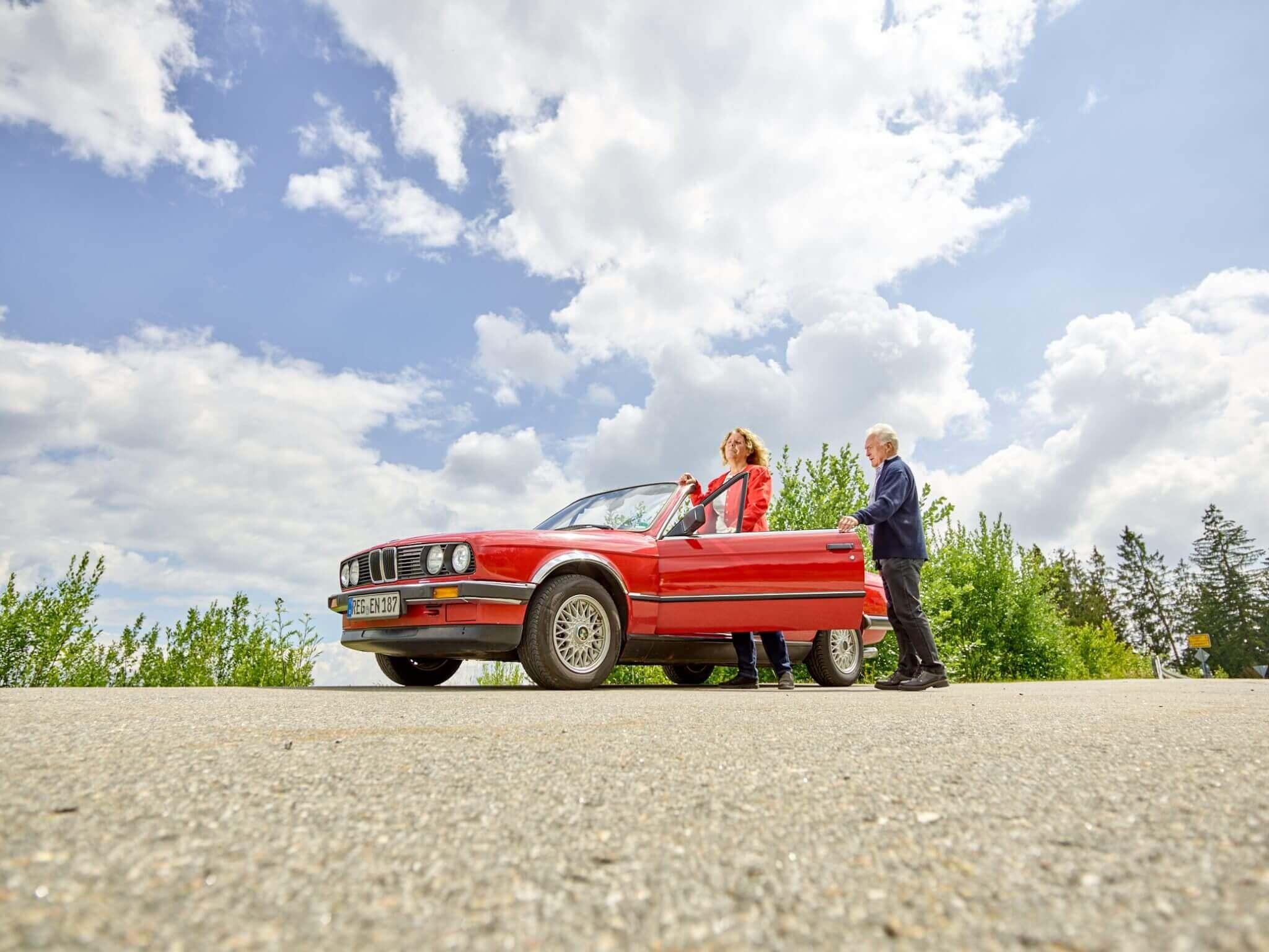 Ein Seniorenpärchen steigt in einen roten Mercedes. Im Hintergrund sieht man Langdorf.